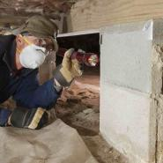 technician examining crawlspace with flashlight